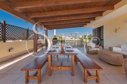 La veranda è arredata con divanetti e un lungo tavolo con panche