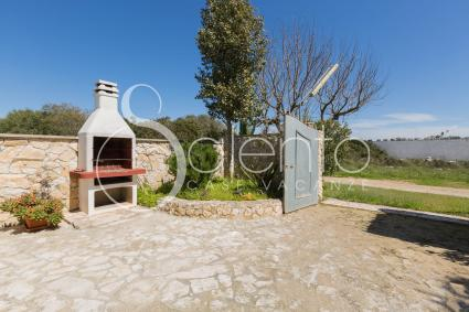 The large garden of the holiday home for rent near the beach, with barbecue grill and parking area