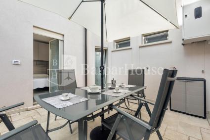 Sul retro del bilocale vi è un pozzo luce ampio, arredato con tavolo e sedie