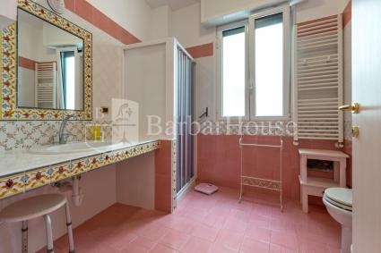 The bathroom with shower and washing machine is spacious and bright