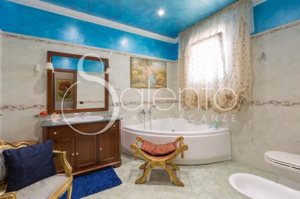In the large bathroom there is a large bathtub