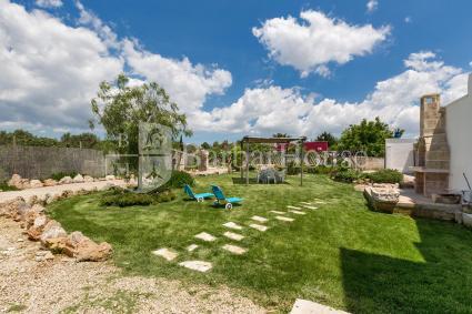 Giardino arredato con gazebo e aree relax più barbecue