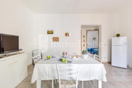 Il chiaro soggiorno ha cucina a vista e sala da pranzo
